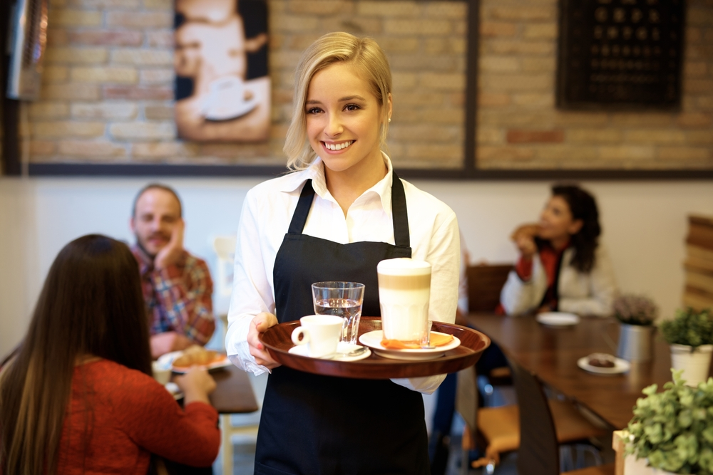 Kellnerin mit Latte Macchiato und Espresso